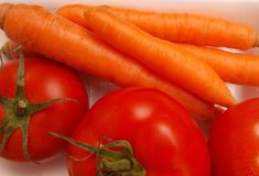 Carrots and tomatoes. Orange carrots and red tomatoes with some green leaves Stock Photography