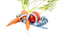 Carrots and tomatoes wrapped in measuring tape Stock Photography