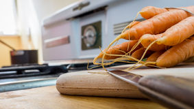 Carrots and vintage stove. An bunch of fresh carrots on wooden cutting board, vintage stove out of focus in the background stock photo