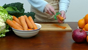 Carrots. A woman peels a carrot stock video footage