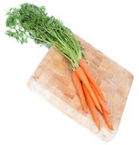 Carrots on wooden board. Isolated Royalty Free Stock Photography