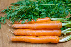 Carrots on a wooden table top Stock Images