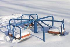 Carrousel du ` s d'enfants qui est enterré dans la neige dans un sunn d'hiver Photo stock
