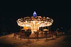 Carrousel lumineux la nuit foncé en hiver Images libres de droits