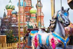 Carrouselpaarden bij de Kerstmismarkt op de achtergrond van St B royalty-vrije stock afbeeldingen
