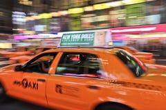 Carrozza di tassì che accelera attraverso la città fotografia stock