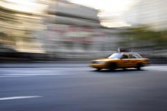 Carrozza di tassì che accelera giù la via in una sfuocatura Immagine Stock