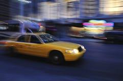 Carrozza di tassì che accelera giù la via in una sfuocatura Fotografia Stock Libera da Diritti