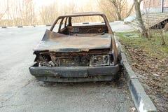 Carrozza ferroviaria bruciata abbandonata vicino alla costruzione di appartamento La Russia fotografia stock libera da diritti