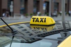 Carrozza gialla con il segno del taxi sul tetto parcheggiato sui passeggeri aspettanti della via della città per prendere  Il tax immagine stock