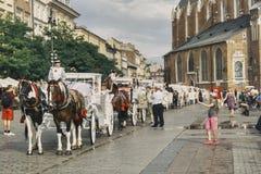 Carrozze bianche per il trasporto dei turisti a Cracovia immagini stock libere da diritti