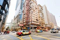 Carrozze commoventi sulla strada affollata con i grattacieli moderni di architettura sulla strada di città Fotografie Stock Libere da Diritti