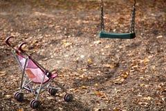 Carrozzina delle bambole sul campo da giuoco vuoto Fotografia Stock