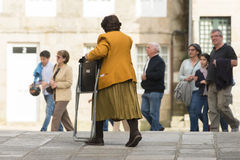 Carruing a chair. PONTEVEDRA, SPAIN - APRIL 2, 2015: A woman walks carrying a folding chair, one of the streets in the historic city center, a sunny day Stock Images