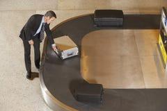 Carrusel de equipaje de Claiming Suitcase At del hombre de negocios en aeropuerto Foto de archivo