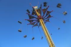 Carrusel del oscilación que vuela contra el cielo azul Imagen de archivo libre de regalías
