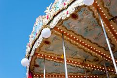 Carrusel del vintage en el fondo del cielo azul brillante de la primavera Imagen de archivo