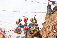 Carrusel en la Navidad justa en el fondo de la GOMA Cuadrado rojo Moscú, Rusia Foto de archivo libre de regalías