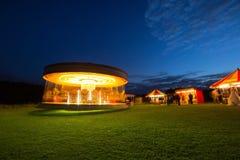 Carrusel en la noche con el funfair Fotos de archivo libres de regalías