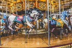 Carrusel francés viejo en un parque del día de fiesta Tres caballos y aeroplanos Imagenes de archivo