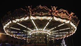 Carrusel iluminado del parque de atracciones del vintage con los caballos de madera que giran en la noche metrajes