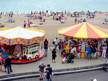 Carrusel y vendedores en la costa de Brighton, Sussex, Inglaterra Imagen de archivo