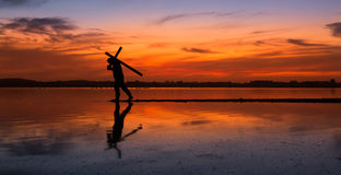 Carry Cross of Faith. Man carrying a cross on a lake, with a fire like sunset in the sky Royalty Free Stock Photos