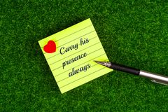 Carry His Presence Always. In memo with heart shape and pen on grass background Stock Photos