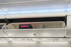 Carry-on luggage in overhead storage compartment on airplane. Stock Photos