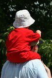 Carry me, Dad. Young child wearing red outfit and hat being carried by father Royalty Free Stock Images