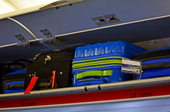Carry-on and Overhead Baggage. In aircraft baggage compartment above the seats stock photos