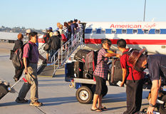 Carry On Valet. Passengers depositing carry on luggage in the valet service on a commuter plane, American Eagle.  While these luggage are approved carry-ons Stock Images