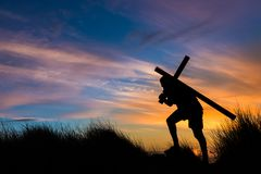 Carry Your Own Cross. Cross getting carried up a hill at sunet Royalty Free Stock Image