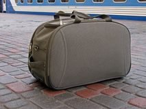 Carryall standing on platform. In front of train Stock Image