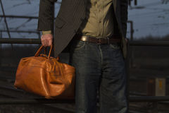 Carrying bag. Man holding leather bag at train station Royalty Free Stock Photo