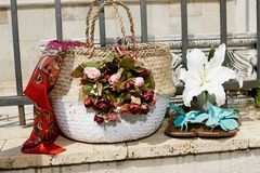 Carrying bag made of raffia braided with floral decoration, light blue flip flops and a white lily flower, set off on a brick wall royalty free stock photography