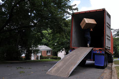Carrying box into moving truck. An unidentifiable person is carrying a heavy moving box up a ramp into the back of a moving truck, on a summer day in typical stock photos