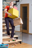 Carrying the boxes. Young careless man on stairs carrying heavy boxes Stock Photo