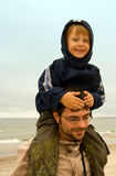 Carrying a Boy. Young father carrying his little son on his shoulders Royalty Free Stock Photos