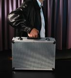 Carrying case. Young man carrying a metal case Royalty Free Stock Images