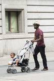 Carrying a child in a baby chair. BRUSSELS, BELGIUM - JULY 4, 2015: A black man, walking carrying a child in a baby chair Royalty Free Stock Photos