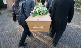 Carrying a coffin. Six peoply are carrying a coffin on to a cemetery Royalty Free Stock Image