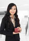 Carrying a cup of tea. Young businesswoman are carrying a cup of tea at the office Stock Photography