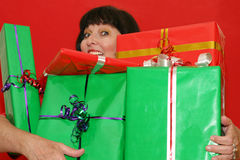 Carrying gifts. Smiling woman, holding gifts. Focus on the gifts, woman is out of focus stock photos
