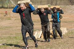 Carrying heavy boxes. RUSSIA, DMITROV REGION, SHUKOLOVO VILLAGE - APRIL 26: Unidentified people is carrying heavy boxes on survival festival game NaPredele (On Royalty Free Stock Image