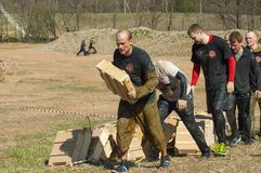 Carrying heavy boxes. RUSSIA, DMITROV REGION, SHUKOLOVO VILLAGE - APRIL 26: Unidentified people is carrying heavy boxes on survival festival game NaPredele (On Stock Photo