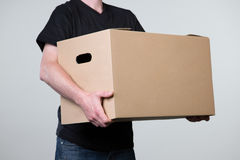 Carrying a heavy cardboard with two hands, isolated on grey. A man is carrying a big cardboard in his hands isolated on a grey background Stock Photos