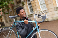 Carrying his bike. Young man carrying his bike royalty free stock images