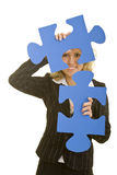 Carrying jigsaw pieces. Blonde business woman holding two oversized jigsaw pieces royalty free stock photos