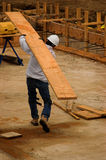 Carrying Lumber. A construction worker carrying a very large board royalty free stock photo